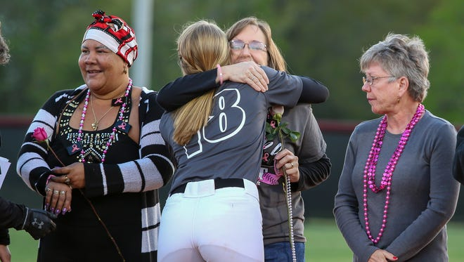 Tate pitcher Hannah Brown gives her aunt, Regina Wood, a cancer survivor, a hug before the start of the 9th annual Strike Out Cancer softball game at Tate High School on Friday, March 23, 2018. Over the years, the event has raised over $75,000 for the American Cancer Society.
