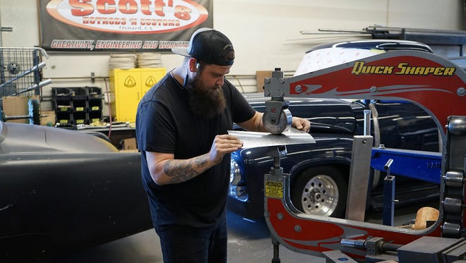 A Scott's Hotrods 'n Customs employee works in the business's current shop in Oxnard, California. Scott's is moving to a larger site in Knoxville in April 2018.