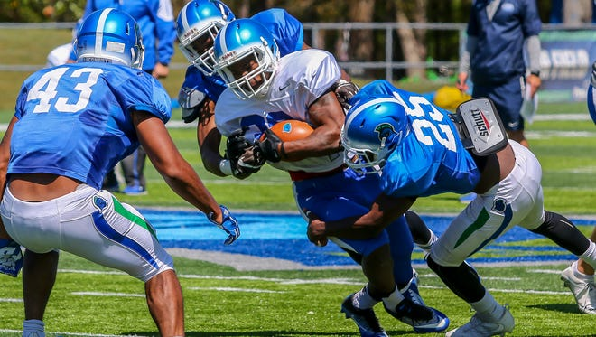 The UWF football team runs through drills during spring practice on Pen Air Field at the University of West Florida on Saturday, March 31, 2018.