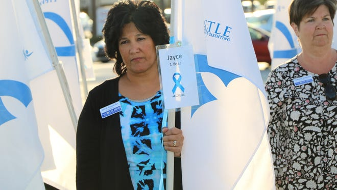 Carol Houwaart-Diez, left, executive director of the United Way of Martin County, was a flag bearer during the Memory Field dedication.