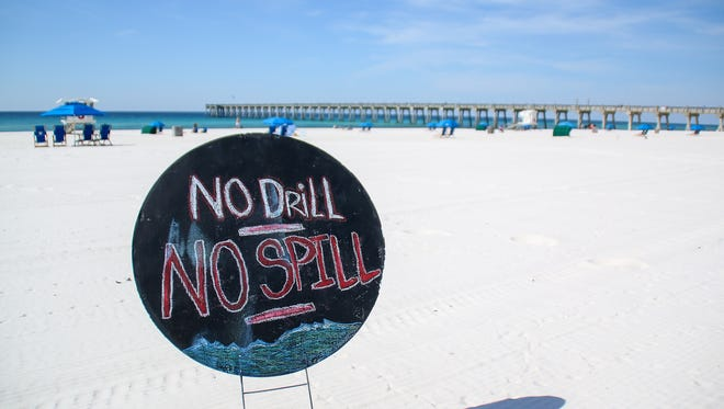 Signs against drilling for oil along the Florida coast are placed in the sand during a press conference on Pensacola Beach on Friday, April 20, 2018. The date marks the 8th anniversary of the BP oil spill, which was caused by an explosion on the Deepwater Horizon drilling rig that was off the coast of Louisiana. The explosion killed or injured more than two dozen workers and led to more than 210 million gallons of oil spilling into the Gulf of Mexico.