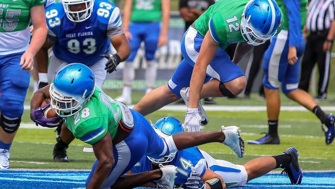 Jemari Ford (28) gets tripped up by Noah Biggs (14) in the Blue & Green spring football game at UWF's Pen Air Field on Saturday, April 21, 2018.