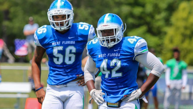 Ricky Richardson (42), a West Florida High School graduate, and Ke'shawn Showers (56), a Pine Forest High School graduate, look to the sideline for the play call in the Blue & Green spring football game at UWF's Pen Air Field on Saturday, April 21, 2018.
