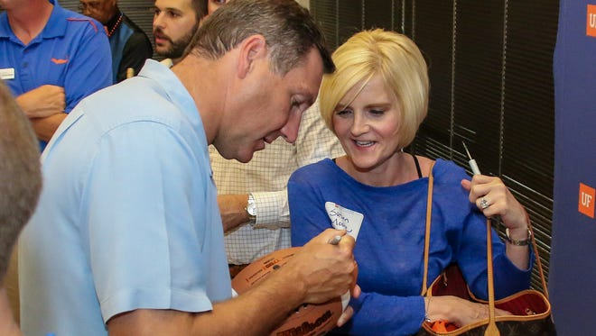 First-year University of Florida head football coach Dan Mullen autographs a football for Susan Moore during the Northwest Florida Gator Club's free Gator Gathering event at Sanders Beach-Corinne Jones Resource Center on Wednesday, May 30, 2018.