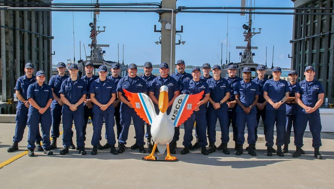 Members of the U.S. Coast Guard pose for a picture with the recently repaired and repainted pelican statue representing them after it was unveiled at the USCG station on NAS Pensacola on Friday, Jun 1, 2018. The statue, which debuted in 2004, was removed from its downtown perch earlier this year to have major fiberglass repairs done to it.