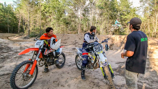 Collin McRaney, 19, of Hattiesburg, Miss., left, Michael Ashe, 26, owner of Atmore Motorsports Park in Atmore, Ala., center, and Josh Neptune, owner of the new MX191 motocross dirt track in Milton, watch as Cody Zollars, 22, of Milton, jumps behind them on Tuesday, July 24, 2018. Located at 8115 Munson Highway, the property is about nine miles northeast of Milton High School and two miles past Bob's Canoe Rentals on Munson Highway. Josh and his wife, Joy, received initial approval for a conditional use permit for the property from the Santa Rosa County Zoning Board on July 12 and are seeking final approval from the Santa Rosa County Board of County Commissioners on Thursday, July 26.