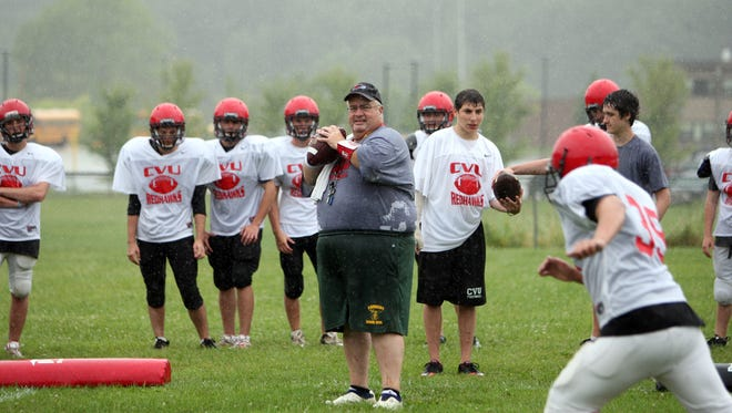 CVU Varsity Football head coach Jim Provost throws to receivers during team drills on the first day of official practice in Vermont on August 15, 2011, in Hinesburg.