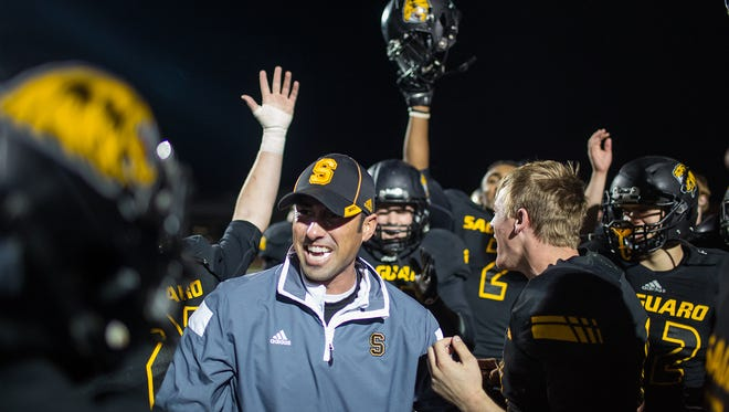 Saguaro head coach Jason Mohns celebrates with the football team after winning its Division III semifinal game against Queen Creek Nov. 21, 2014 at Phoenix Arcadia.