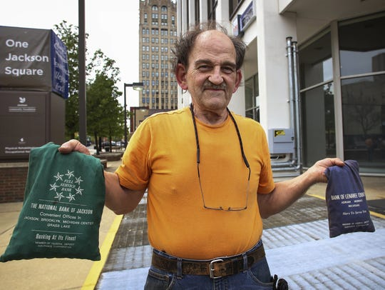Brian McGonegal poses with 2,700 pennies in downtown