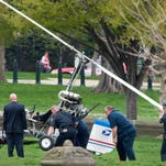 Capitol Hill police officers and other officials lift a gyrocopter that landed on the U.S. Capitol lawn.