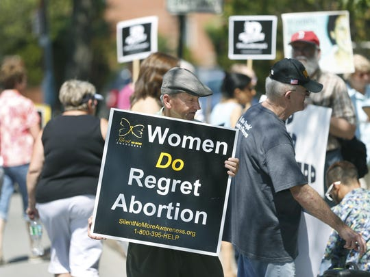 Dick Bobowski of Williamson, Wayne County, holds a sign opposing abortion during a rally to call on New York state officials to investigate and defund Planned Parenthood.