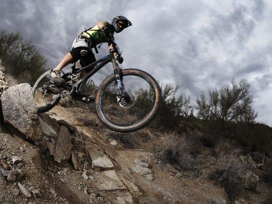 Man mountain biking down steep rocky path, low angle view