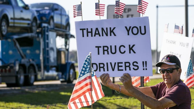 A man holds up a sign as part of a group of SummerGlen residents showing their support for truckers at a weigh station on Interstate 75 on May 1.