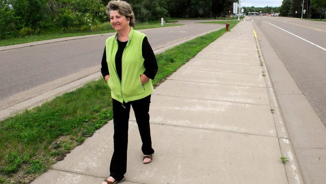 Little Falls Mayor Cathy VanRisseghem walks on a portion of an existing trail in Little Falls near City Hall on Thursday.
