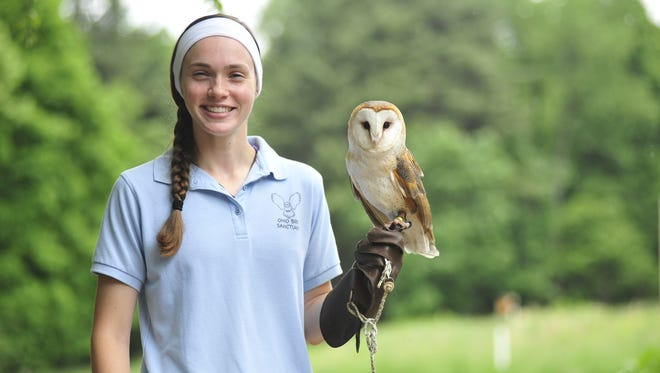 Emily Smith holds Monty, an 8-year-old barn owl at the Ohio Bird Sanctuary.