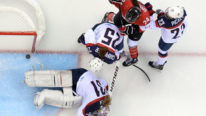 Canada's Natalie Spooner (red jersey) scores a goal during the Women's Ice Hockey Group A match between Canada and USA at the Sochi Winter Olympics on Wednesday.