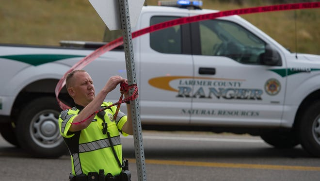 A Fort Collins Police community service officer works to close Centennial Drive at County Road 42C after multiple crashes near Horsetooth Reservoir on Tuesday, July 25, 2017.