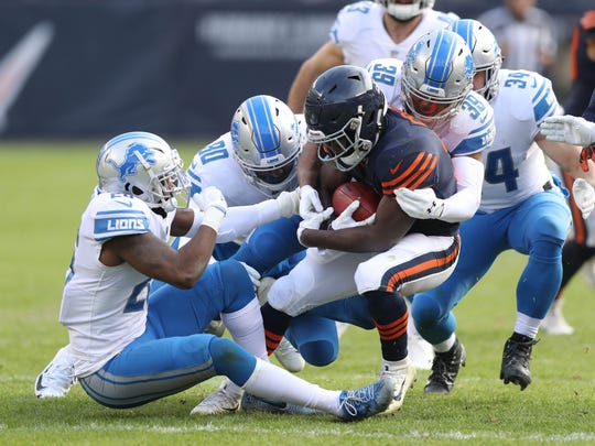 Detroit Lions defenders tackle the Chicago Bears' Tarik Cohen in the third quarter of the Lions' 27-24 win Sunday, Nov. 19, 2017 at Soldier Field in Chicago.