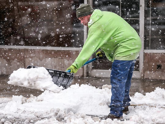 A crew member from Engledow Group shovels mounds of snow from the sidewalks in Downtown Indianapolis on Saturday, March 24, 2018. The National Weather Service reported more than 10 inches of snow fell on Indianapolis that day.