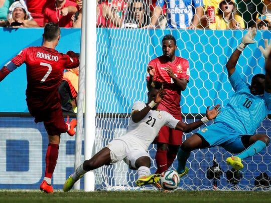 Portugal's Cristiano Ronaldo scores past Ghana's goalkeeper Fatau Dauda and John Boye in their World Cup match Thursday.