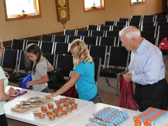 Mayor Kirksey packing backpacks with other volunteers