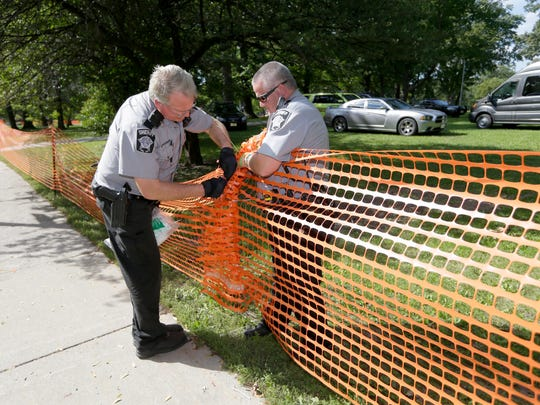Milwaukee County sheriff's deputies work on putting the fencing back up around Sherman Park on Sunday.