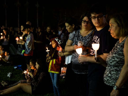 Jasmine Battifora, 6, center, watches her candle flicker during a candlelight vigil at Betti Stradling Park in Coral Springs, Fla., on Monday, Feb. 19, 2018. The Florida PTA organized a statewide candlelight vigil at 7 p.m. to honor the 17 victims of the Marjory Stoneman Douglas High School shooting.