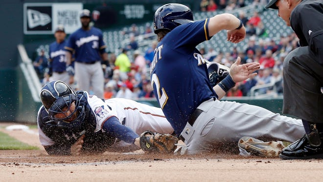 Milwaukee Brewers' Scooter Gennett, right, beats the tag by Minnesota Twins catcher John Ryan Murphy to score from third on a sacrifice fly by Chris Carter in the first inning of a baseball game Tuesday, April 19, 2016, in Minneapolis. (AP Photo/Jim Mone)