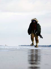 Bundled up against the cold and wind, Winooski native Jason Dion, who now lives in Alaska, walks across a frozen bay on Lake Champlain during an ice-fishing trip with a friend. Dion said ice fishing in Vermont is better than in Alaska because there's a wider variety of fish to catch.