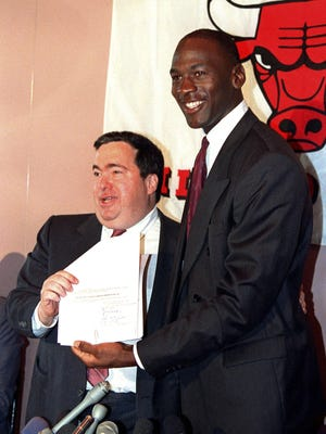 Chicago Bulls' Michael Jordan, right, is all smiles after he signed a new contract as general manager Jerry Krause looks on during a news conference.