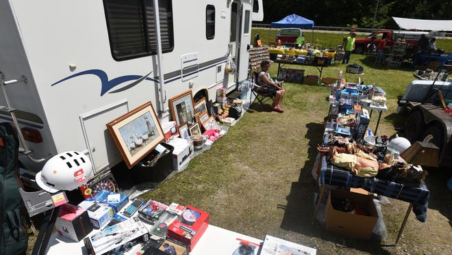 Anita Jones sits outside her camper during the National Road Yard Sale along US 40 west of Zanesville in this Times Recorder file photo. This year's sale has been postponed until August, due to the coronavirus.