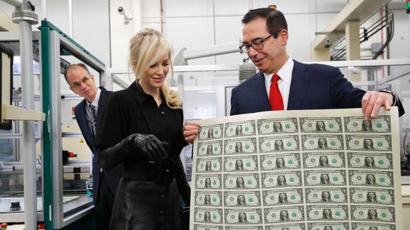 Treasury Secretary Steven Mnuchin, right, shows his