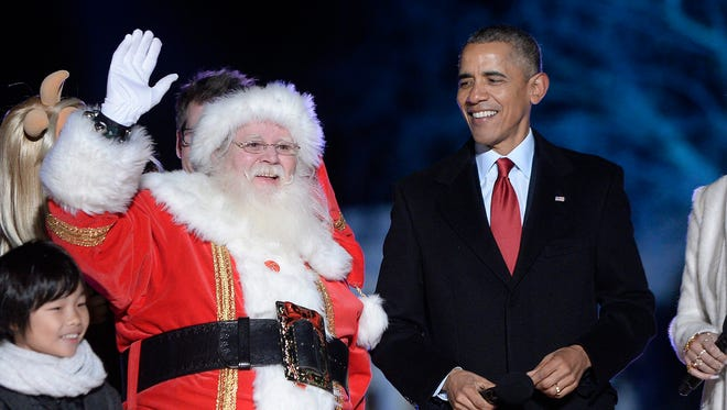 President Barack Obama and Santa Claus wave from the stage during the national Christmas tree lighting ceremony on the Ellipse south of the White House in Washington, DC.