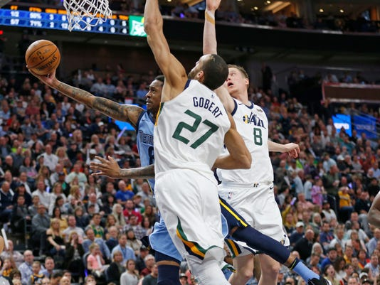 Utah Jazz's Rudy Gobert, left, and Jonas Jerebko, right, defend as Memphis Grizzlies MarShon Brooks, center, goes to the basket in the first half during an NBA basketball game Friday, March 30, 2018, in Salt Lake City. (AP Photo/Rick Bowmer)
