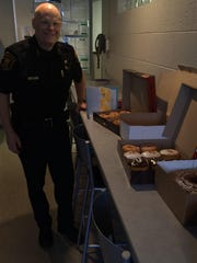 Assistant Police Chief Matt Koehn shows off just a sampling of the treats that have come in lately to the police station.
