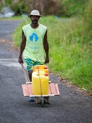 Zaccheus Bruney, 43, pushes several containers of water from a nearby spring up the steep hills of Salybia, Dominica in the Carib Territory belonging to the natives of the region. Bruney's home was completely destroyed by the hurricane as he slowly collects materials to rebuild his home.