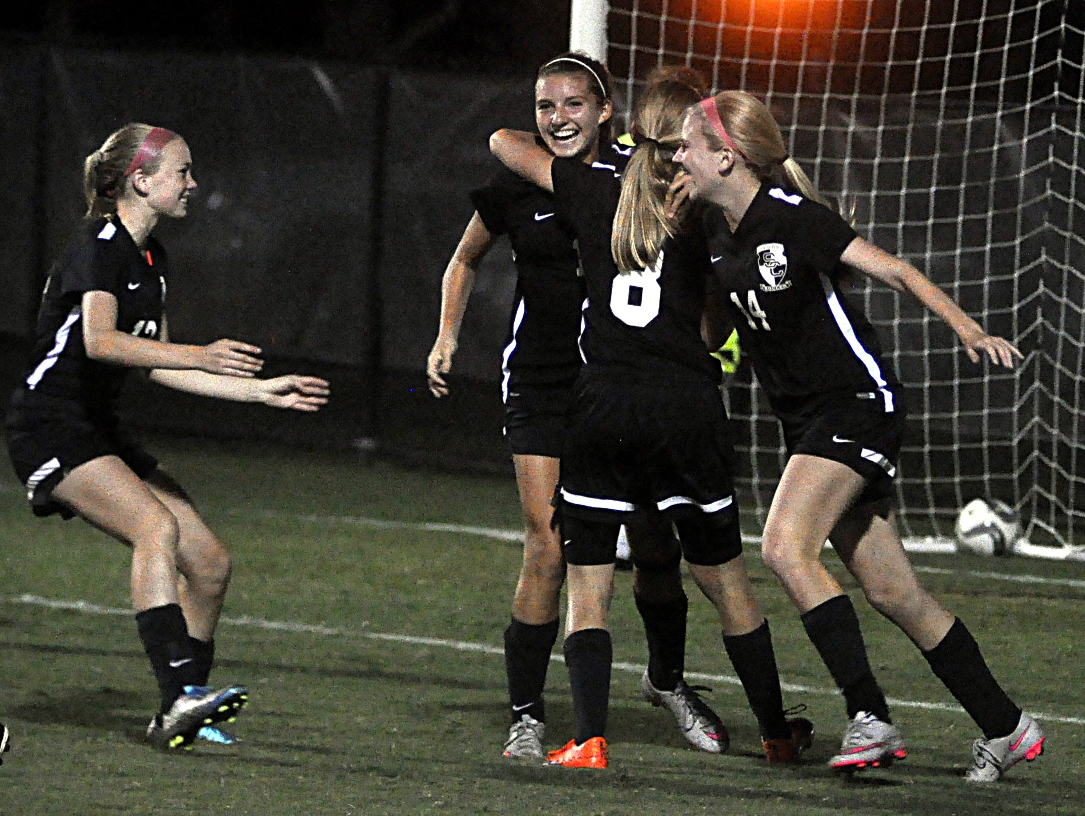 Station Camp sophomore Carolyn Fitch (left), freshman Michaela Nicholson (8) and sophomore Morgan Appenrott (14) celebrate with freshman Meagan Lombardi following Lombardi's game-tying goal during second-half action.
