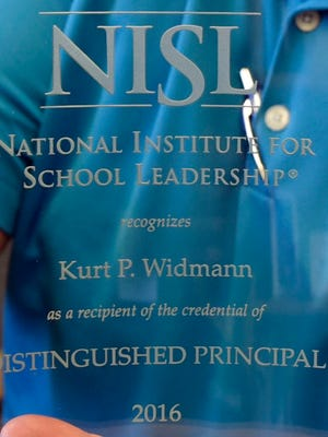 Kurt Widmann holds his National Institute for Social Leadership Distinguished Principal award he was awarded in a recent conference. Widmann is the principal at Chambersburg Area Middle School North.