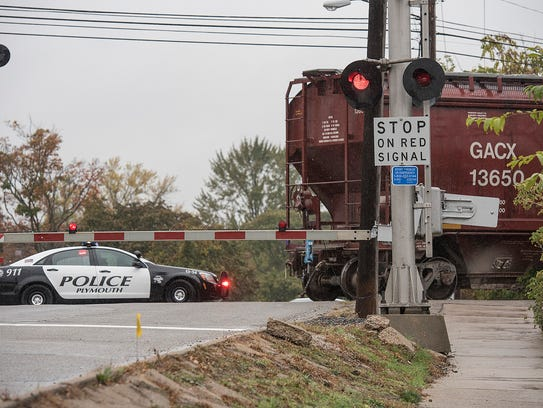 A city police car warns motorists of the train situation. After the police car left, several motorists could be seen driving around the gates at this location on Ann Arbor Trail.