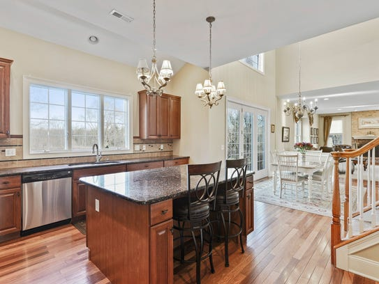 The kitchen includes a rear staircase and a sunny two-story