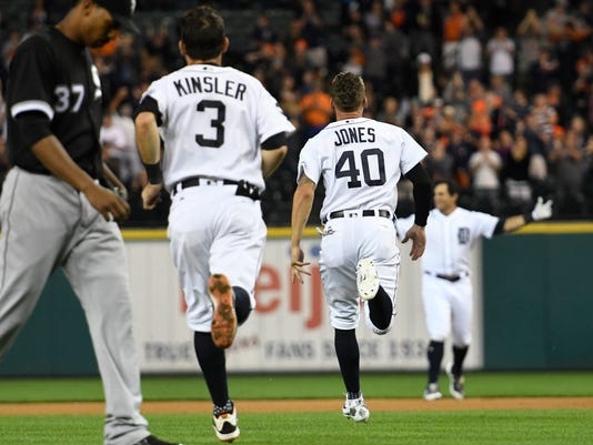 Chicago White Sox relief pitcher Juan Minaya (37) walks to the dugout as Detroit Tigers' Ian Kinsler (3) and JaCoby Jones (40) run into right field to congratulate Mikie Mahtook after his single in the ninth inning of a baseball game, Friday, Sept. 15, 2017, in Detroit. The Tigers defeated the White Sox 3-2. (AP Photo/Jose Juarez)