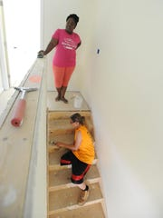 Latiesha Puzzo (left) and her wife, Natalie Puzzo, paint their new home in downtown Dover Thursday. Habitat for Humanity is building five homes on the block.
