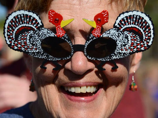 Vicki Tompkins wears turkey sunglasses to Pete's Thanksgiving Block Party on Thursday, Nov. 24, 2016, in Neptune Beach, Fla. People jammed First Street in front of Pete's Bar enjoying beverages and some wearing festive hats and outfits.