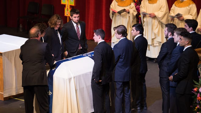 Pallbearers assemble to remove the casket of Mark Dombroski during his funeral mass at Archmere Academy in Claymont.