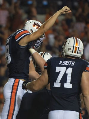 Auburn offensive lineman Mike Horton (64) lifts up Auburn place kicker Daniel Carlson (38) after he scored a touchdown during the first half of the NCAA football game Saturday, Sept. 10, 2016, at Jordan Hare Stadium in Auburn, Ala. Albert Cesare / Advertiser