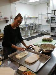 Chef Emily Thibodeau prepares food for the Nourish