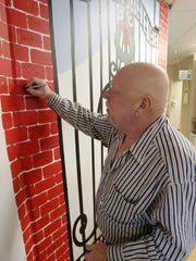 Patient Patrick Laitinen signs his name to the mural