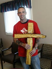 Tim Martinez crafted a wood cross that hangs on the wall of Samaritans Hand in Sheboygan. His skills as a craftsman serve him well in his new job in construction.
