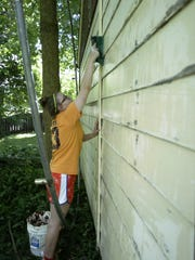 Emma LaBudde washes the siding of a garage before painting it on Monday during a three-day service week coordinated by area Catholic churches to help homeowners in need of assistance maintain their homes and yards.