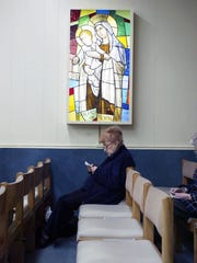 A woman at prayer before Mass in the Chapel in the Bergen Mall in March 2003.